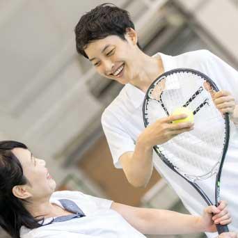 テニスを教えるコーチと習う女性